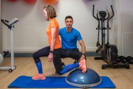Séance de coaching à domicile, exercice en salle, fente sur Bosu